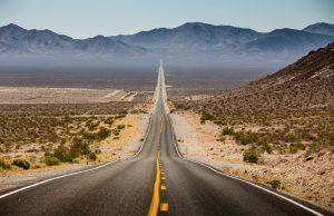 panorama view of an endless straight road running through the barren scenery of the American Southwest with extreme heat haze on a beautiful sunny day with blue sky in summer