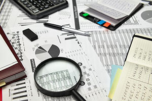 Top view of office employee's desk - work with financial reports, analysis and accounting, tables and graphs, various office items for bookkeeping