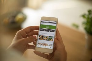 Woman using meal delivery service through mobile app